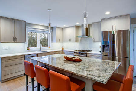 Gorgeous kitchen design features ivory kitchen cabinets flanking modern steel kitchen hood, linear marble tile backsplash, kitchen island with granite counter top and red leather barstools.