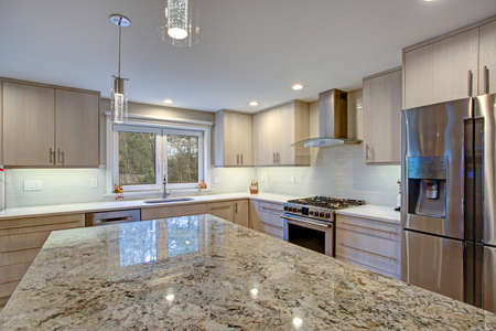 Lovely kitchen room interior features ivory cabinets accented with lucite pulls, white quartz countertop, linear tile backsplash, bar style kitchen island  and modern stainless steel appliances.