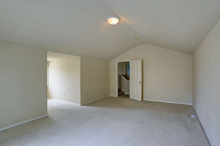 Empty upstairs room with vaulted ceiling, beige walls paint color and carpet floor.