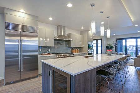 Schlankes, modernes Küchendesign mit einer Küchenhalbinsel, die mit einer grau-weißen Quarzplatte, einem großen Kühlschrank und einer Edelstahlhaube ausgestattet ist. Standard-Bild
