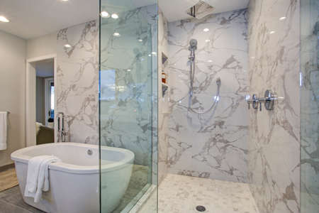 White and gray calcutta marble bathroom design with custom soaking tub and glass walk in shower. Foto de archivo