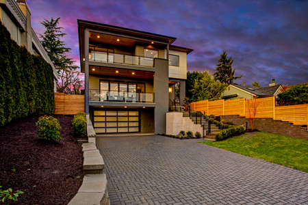 Luxury modern home exterior at sunset boasts four car garage with wide driveway.  写真素材