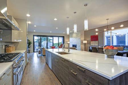Schlankes, modernes Küchendesign mit einer Küchenhalbinsel, die mit einer Arbeitsplatte aus grauem und weißem Quarz ausgestattet ist. Standard-Bild