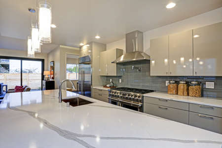 Sleek modern kitchen design with a kitchen peninsula fitted with a gray and white quartz countertop, huge refrigerator and stainless steel hood.