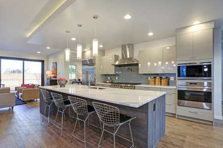 Schlankes, modernes Küchendesign mit einer Küchenhalbinsel, die mit einer grau-weißen Quarzplatte, einem großen Kühlschrank und einer Edelstahlhaube ausgestattet ist.