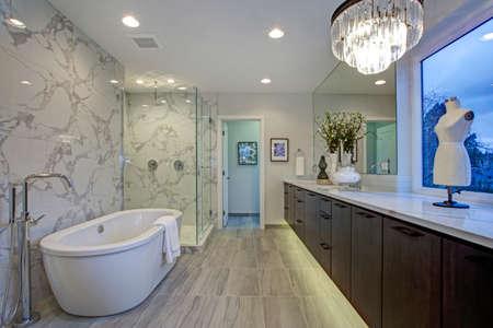 Conception de salle de bain en marbre calcutta blanc et gris avec planchers radiants, comptoirs en quartz, armoires flottantes et baignoire autoportante.