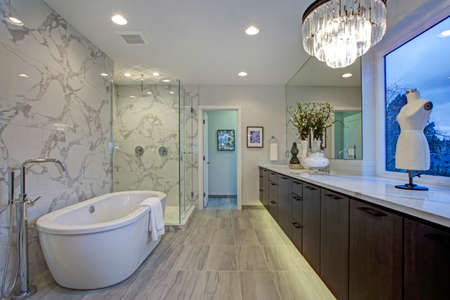 White and gray calcutta marble bathroom design with radiant floors, quartz counters, floating cabinets and freestanding tub.