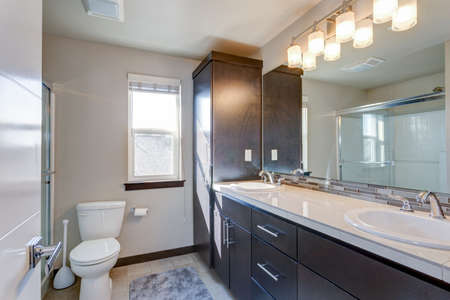 Newly renovated bathroom in apartment building with dual vanity cabinet.
