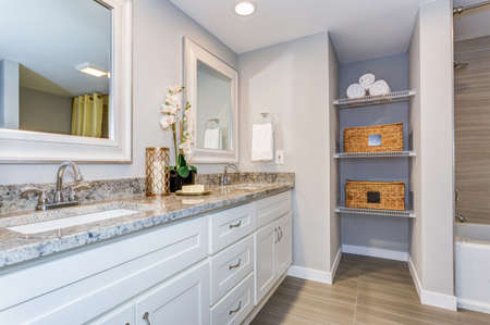 Elegant bathroom with long white vanity cabinet, granite counter top, two sinks and built in shelves.