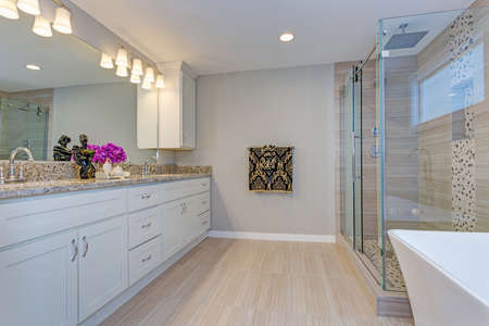 Light modern bathroom design with long dual vanity cabinet, glass shower and freestanding tub.
