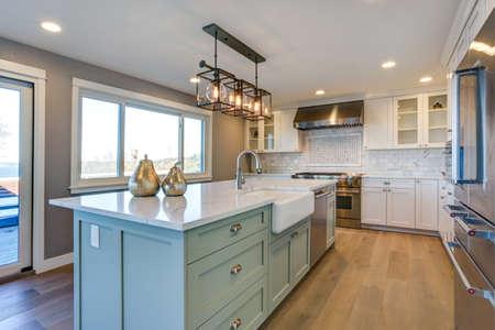 Piękny pokój kuchenny z zieloną wyspą i zlewem.