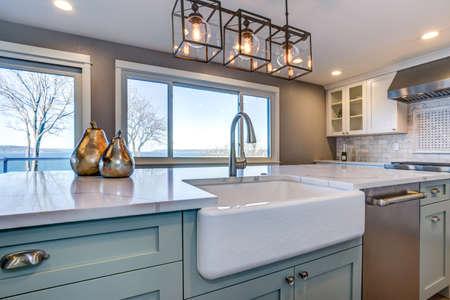 Schönes Küchenzimmer mit grüner Insel und Bauernspüle. Standard-Bild