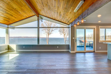 Empty room with planked vaulted ceiling and scenic water view.