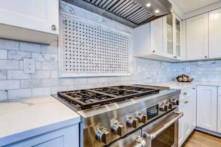 White Kitchen with stainless steel hood over gas cooktop and carrera marble backsplash. Stock Photo