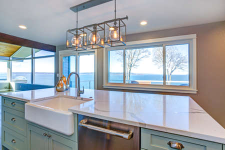 Beautiful kitchen room with green island, farmhouse sink and gorgeous water view.