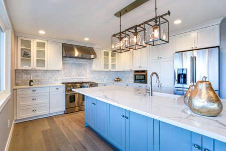 Bella cucina bianca con grande isola in marmo.