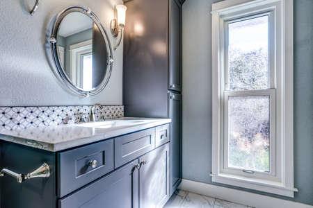 New fresh bathroom with blue vanity, mosaic backsplash and a cabinet alongside marble floor.
