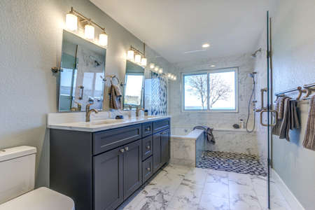Luxury bathroom interior with blue dual washstand atop marble floor.