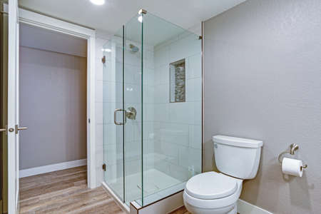 Elegant bathroom with glass shower and hardwood floor. Foto de archivo