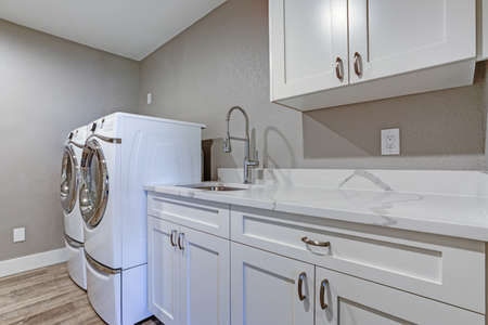 Laundry room with taupe walls, white cabinets and marble top counters.