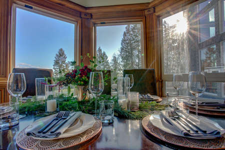 Elegant table set for dinner with beautiful view from the windows.