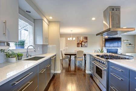 Cocina elegantemente renovada con encimeras de cuarzo y electrodomésticos de acero inoxidable.