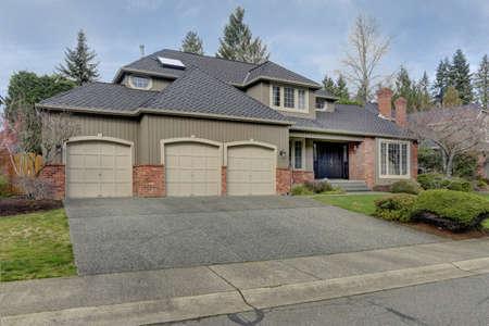 Luxury brick home exterior with three car garage.