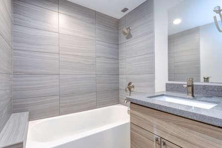 Interior del cuarto de baño moderno gris después de la remodelación.