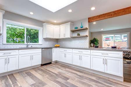Open concept kitchen with white cabinets, grey quartz countertops and tile backsplash. Фото со стока