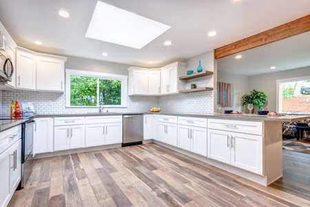 Open concept kitchen with skylight, white cabinets and hardwood floor. Stok Fotoğraf