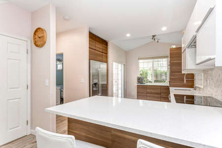 Awesome kitchen room with quartz countertops, new wooden cabinets and modern laminate floor.