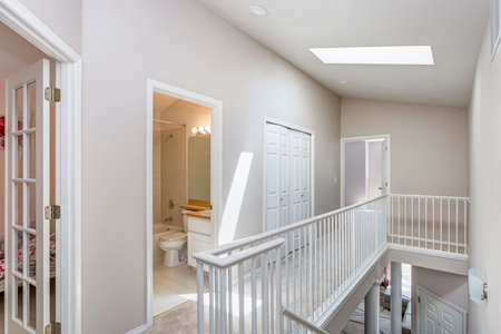 Light beige hallway with skylight and staircase.