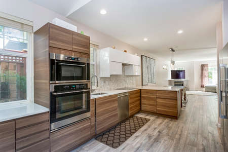 Awesome kitchen room with quartz countertops, new wooden cabinets and modern laminate floor. Stock Photo