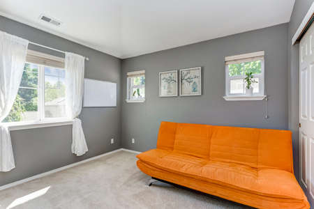 Grey room interior with orange sofa and high vaulted ceiling. Banque d'images