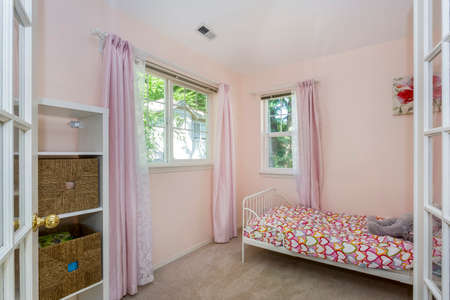 Amazing girl's bedroom with pink window curtains. Banque d'images