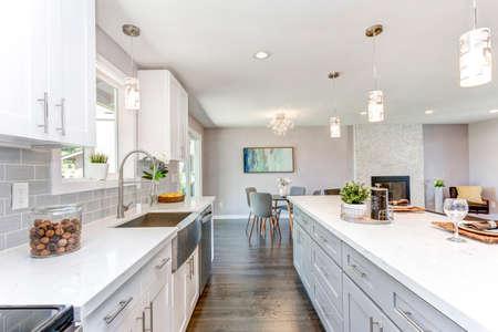 Superbe cuisine avec plan d'étage à aire ouverte, armoires blanches et immense îlot. Banque d'images - 107742918