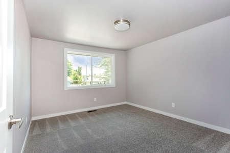 Small empty room with a window and grey carpet floor. Banque d'images