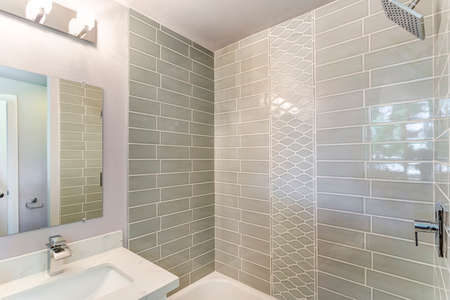 Well designed bathroom interior with mosaic tiled wall.