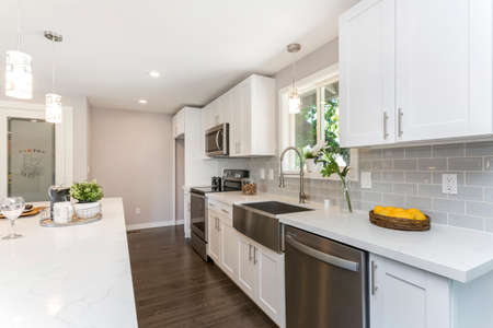 Gorgeous kitchen with open concept floorplan, white cabinets and farm sink. 免版税图像