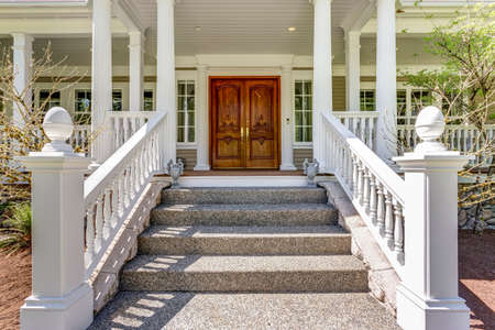 Entrance to a luxury country home with covered deck, white columns and staircase. Banque d'images