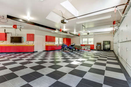 Spacious modern garage interior with checkerboard floor and red storage system.