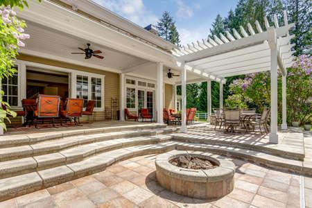 Heerlijk buitenterras met witte pergola, vuurplaats in de achtertuin van een luxe huis.