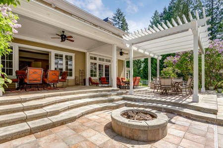 Lovely outdoor deck patio space with white pergola, fire pit in the backyard of a luxury house. 스톡 콘텐츠 - 107897680