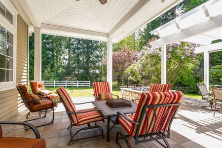 Spacious covered deck area with table and red outdoor chairs under white plank ceiling.