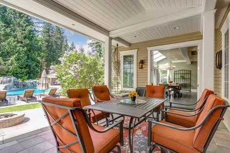 Ruim overdekt terras met tafel en rode buitenstoelen onder plafond van witte planken.