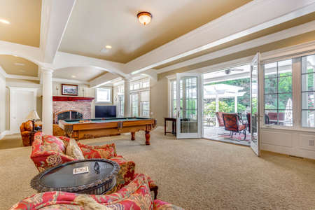 Spacious game room with white columns, billiard table and exit to outdoor patio. Banque d'images - 107897683