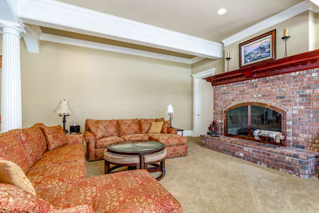 Living room with red brick fireplace and large colorful sofa