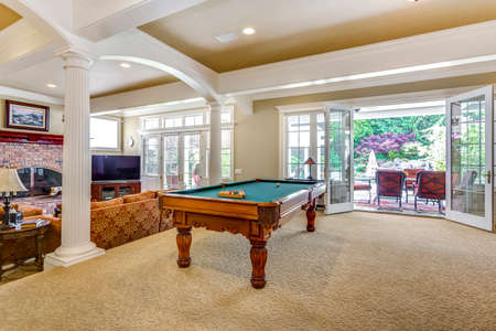 Spacious game room with white columns, billiard table and exit to outdoor patio.