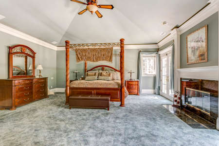 Luxury master bedroom with canopy bed and fireplace 免版税图像 - 107897690