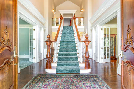 Grand two story foyer with elegant staircase and colorful rug on the floor.